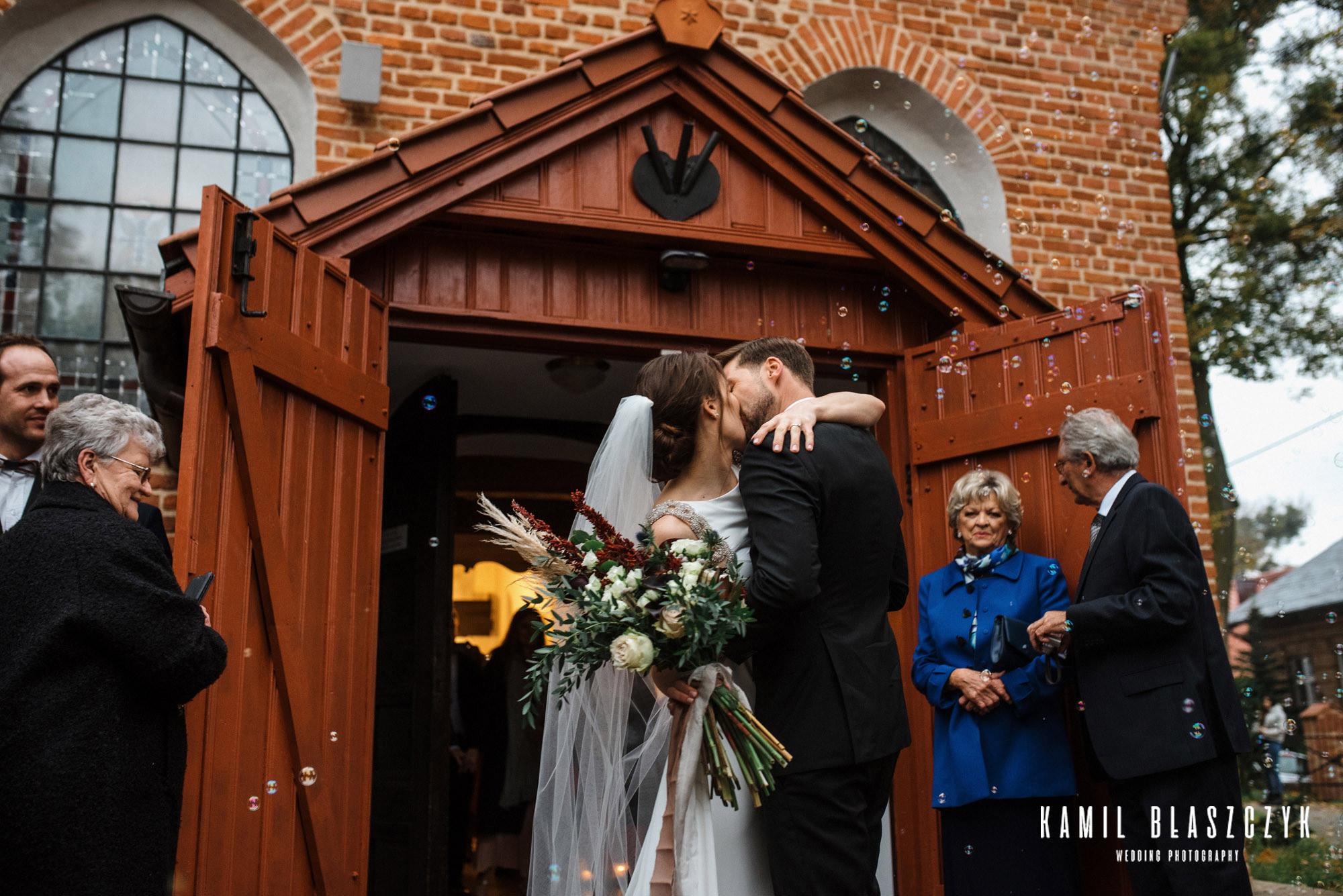 Pocałunek pod kościołem po ślubie Moniki i Kobusa