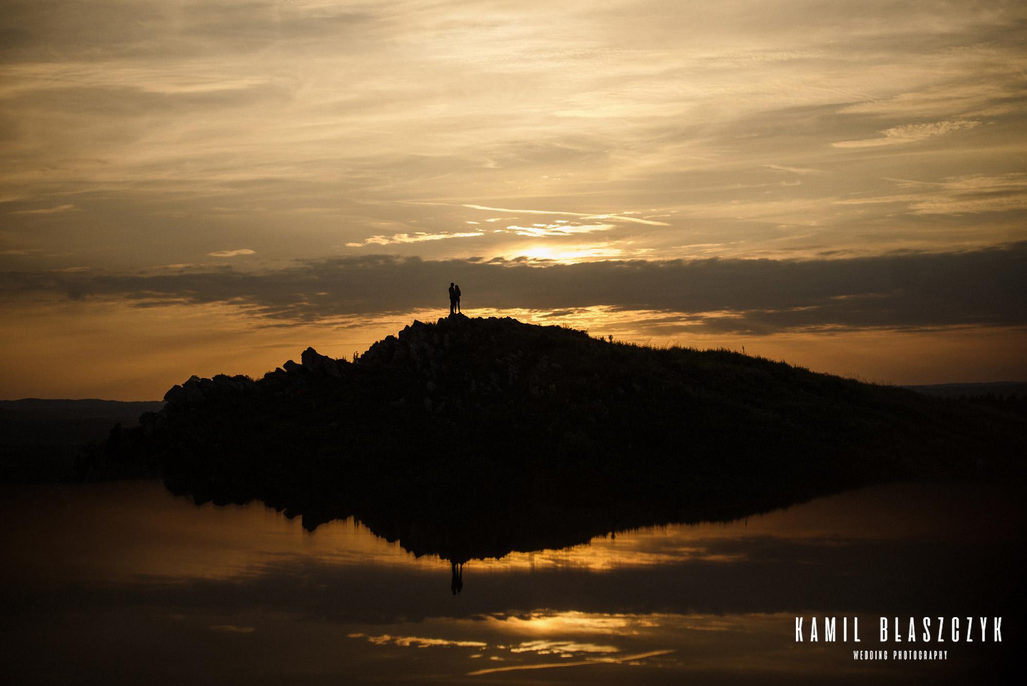 Para zakochanych stojących na górze w miejscowości Miedzianka podczas zachodu słońca, sfotografowani przez fotografa ślubnego Kamila Błaszczyka
