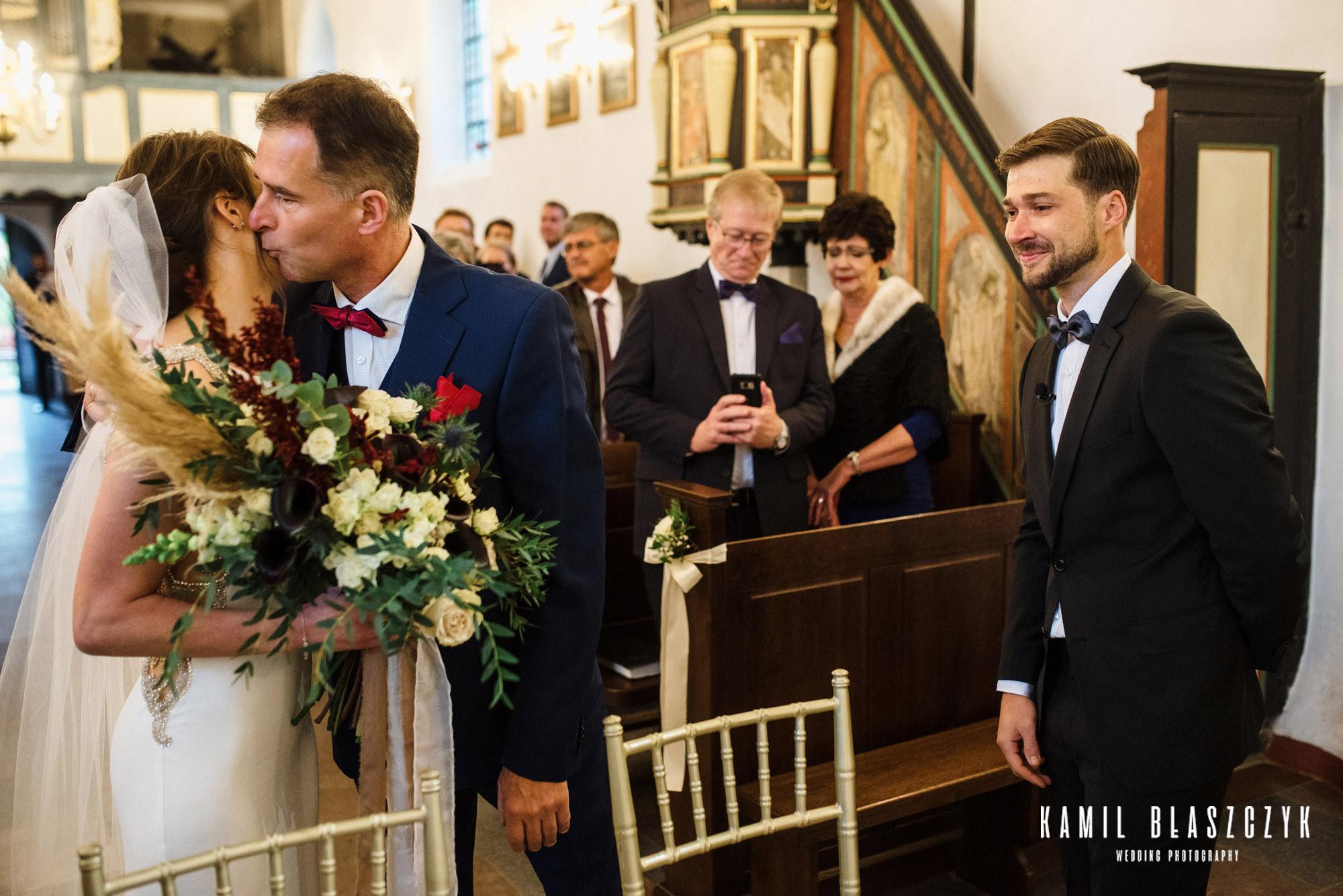zdjęcia ślubne w kościele, oddanie córki przez Ojca podczas ceremonii ślubu Moniki i Kobusa